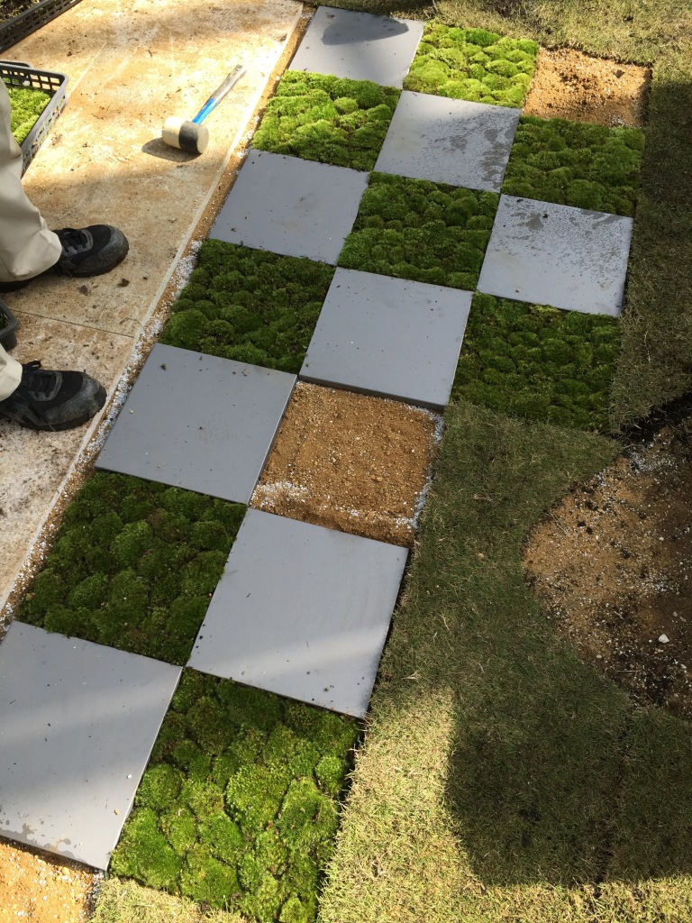 Laying tiles, both of stone and moss