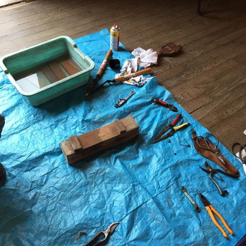 The materials for the sharpening all laid out. You begin with a rough stone and use several that become more fine textured. Then you finish by running your blade over newspaper