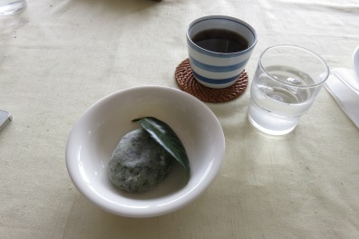 Homemade mochi, using fresh artemisia shoots to flavor and garnished with a glossy camellia leaf